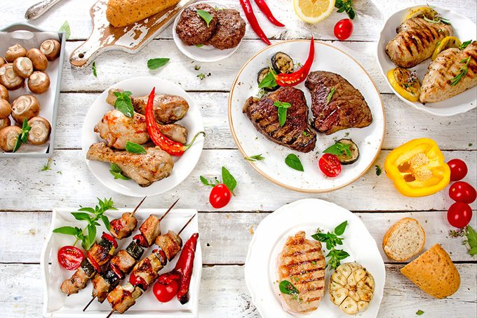 Assorted grilled meats and vegetables on a white wooden table