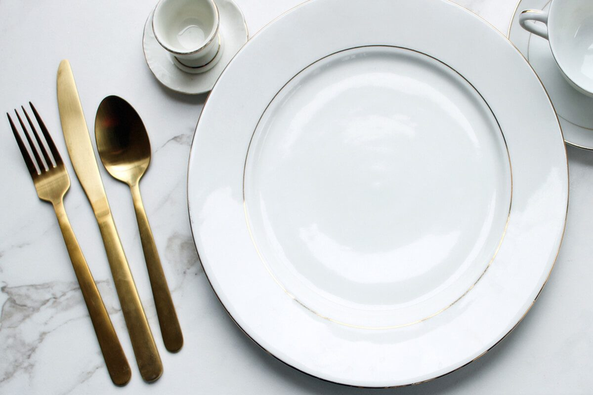 Over head flat lay view of white and gold fine china place setting. Gold silverware & How to Set a Table | Taste of Home