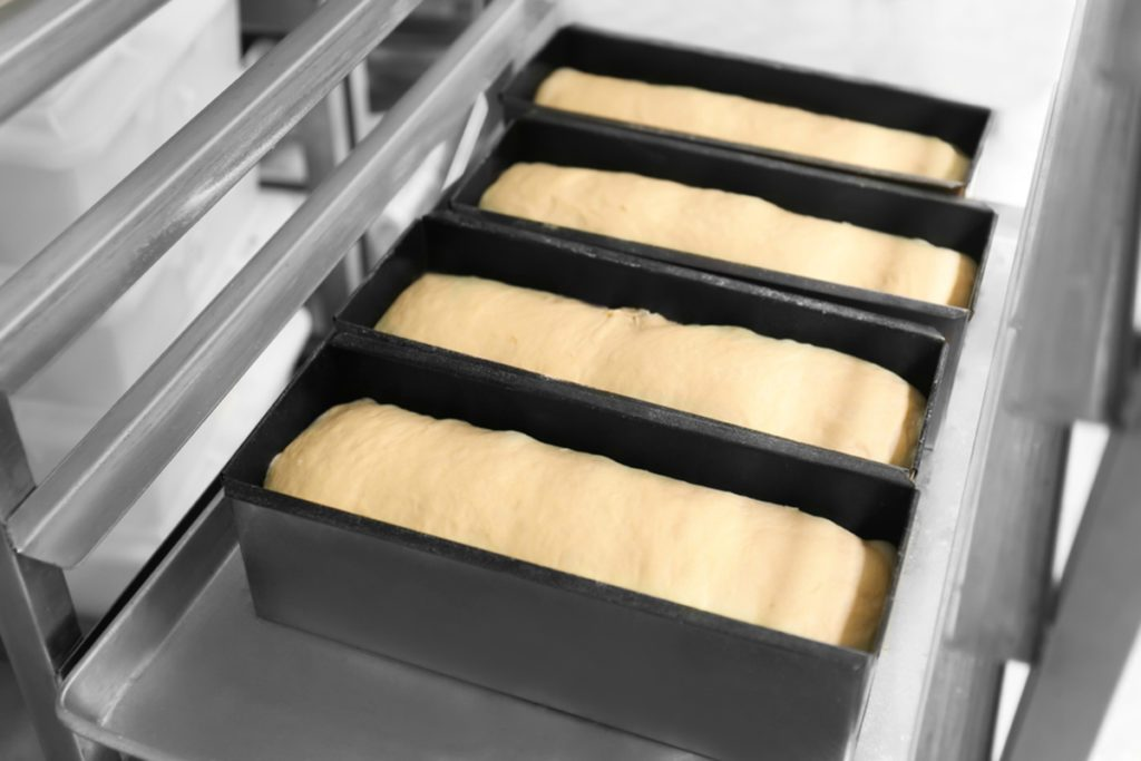 Loaf tins with uncooked bread in bakery