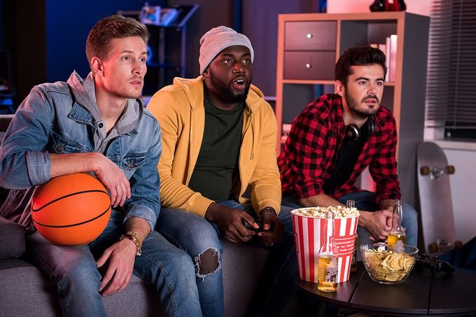 So exciting. Three young interested guys are sitting on sofa and expressing exhilaration while watching sport game with opened mouthes. Friends are eating popcorn and drinking beer