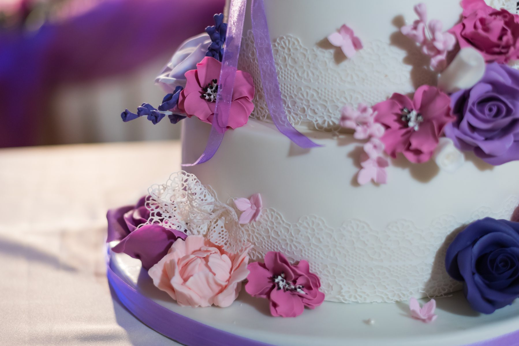 Beautiful fondant covered cake decorated with edible lace and bouquet of purple flowers