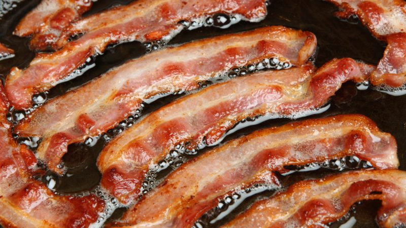 Bacon strips or rashers being cooked in frying pan.; Shutterstock ID 153808931