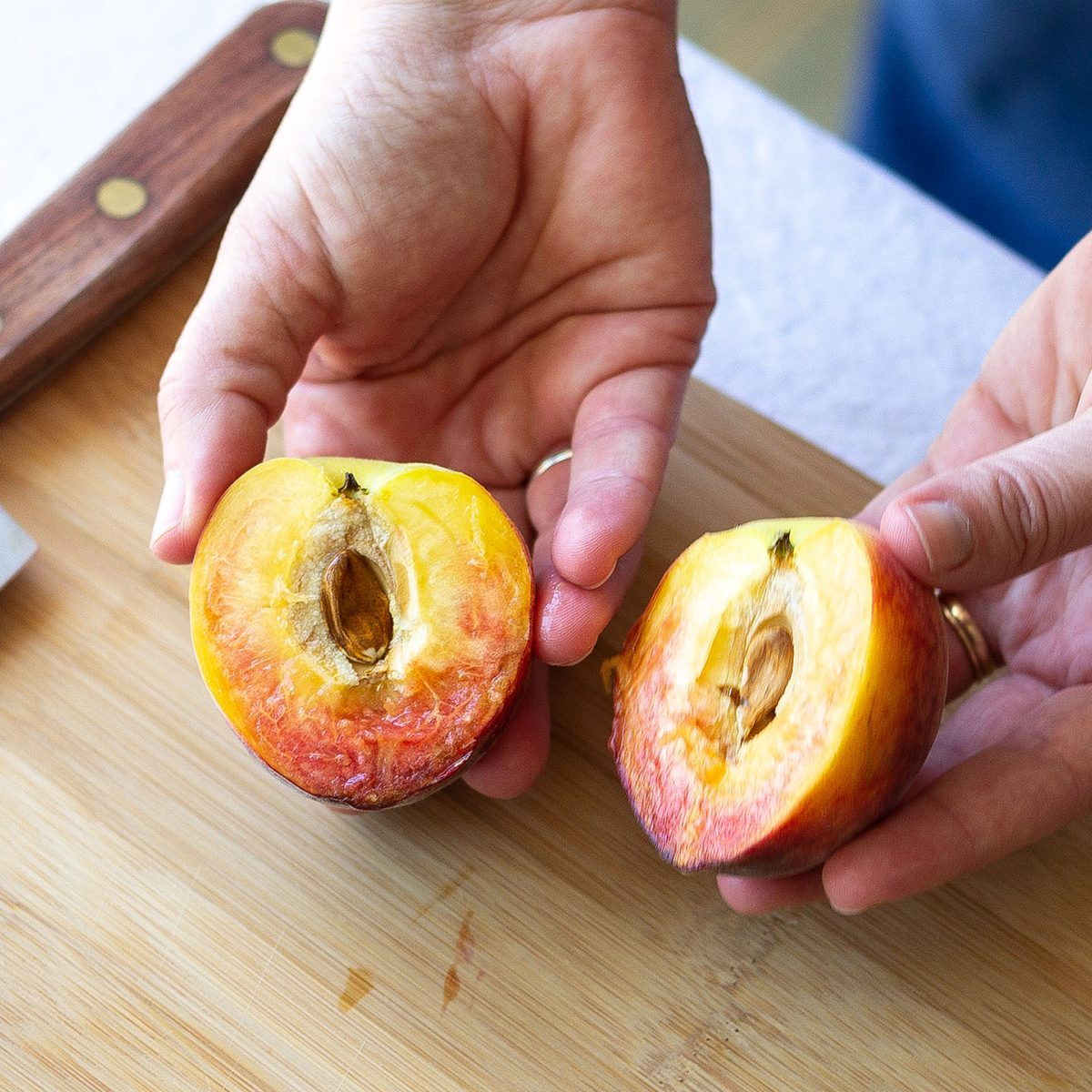 Two hands holding two halves of a fresh peach.