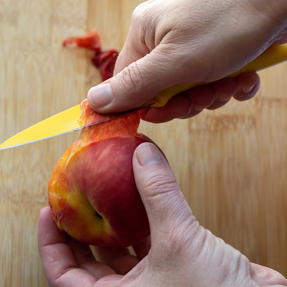 Using a yellow paring knife to peel skin from a blanched whole peach.