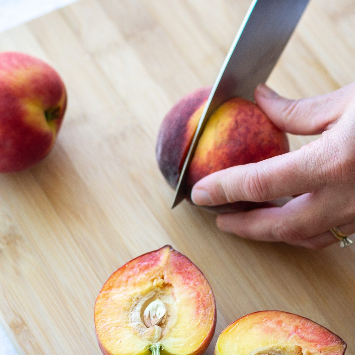 Slicing a whole peach in half on a cutting board with a cut peach nearby.