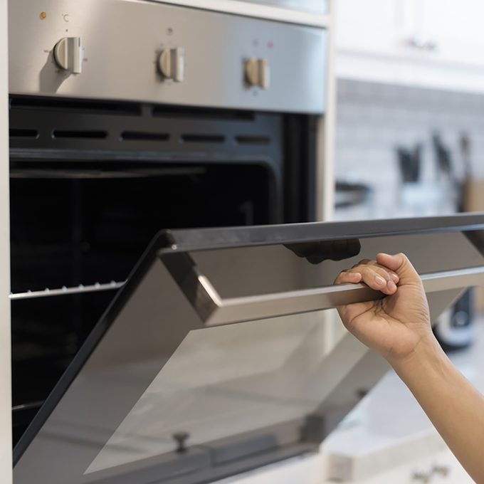 Hands open the oven in the kitchen