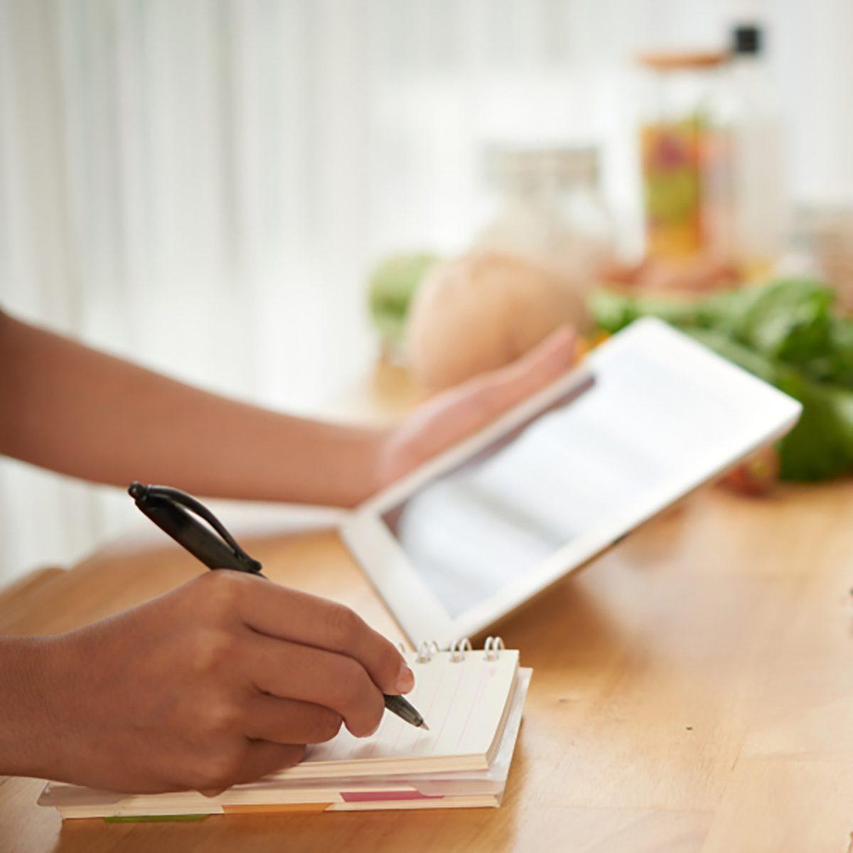 Hands of woman composing healthy menu for upcoming week;