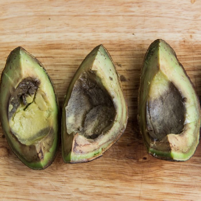 Four pieces of rotten avocado on wooden background top view; Shutterstock ID 1051896014