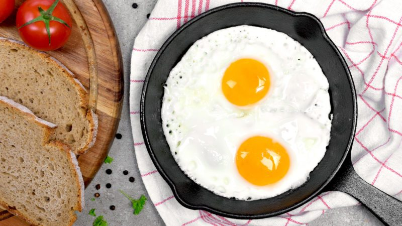 Delicious fried eggs in a cast iron pan. Top view of eggs and bread, breakfast