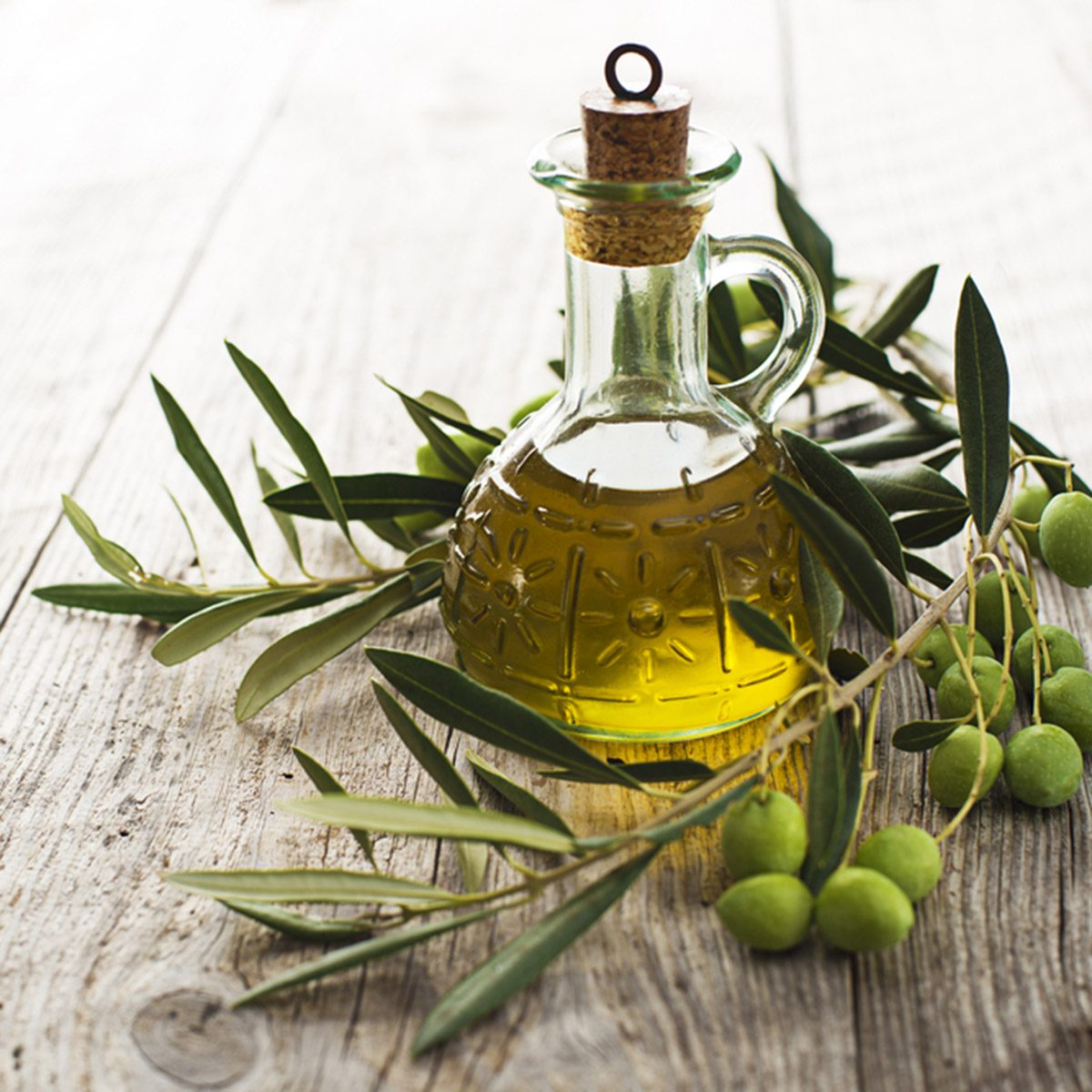 Olive oil and olive branch on the wooden table; Shutterstock ID 159233054