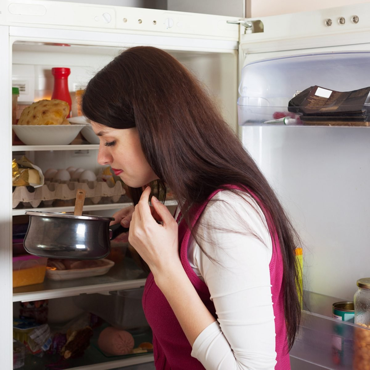 Brunnette woman holding foul food near refrigerator at home; Shutterstock ID 215612881; Job (TFH, TOH, RD, BNB, CWM, CM): TOH