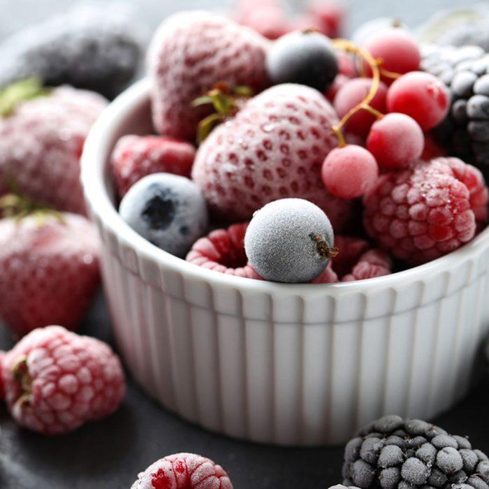 Frozen berries on a black wooden table; Shutterstock ID 476031883