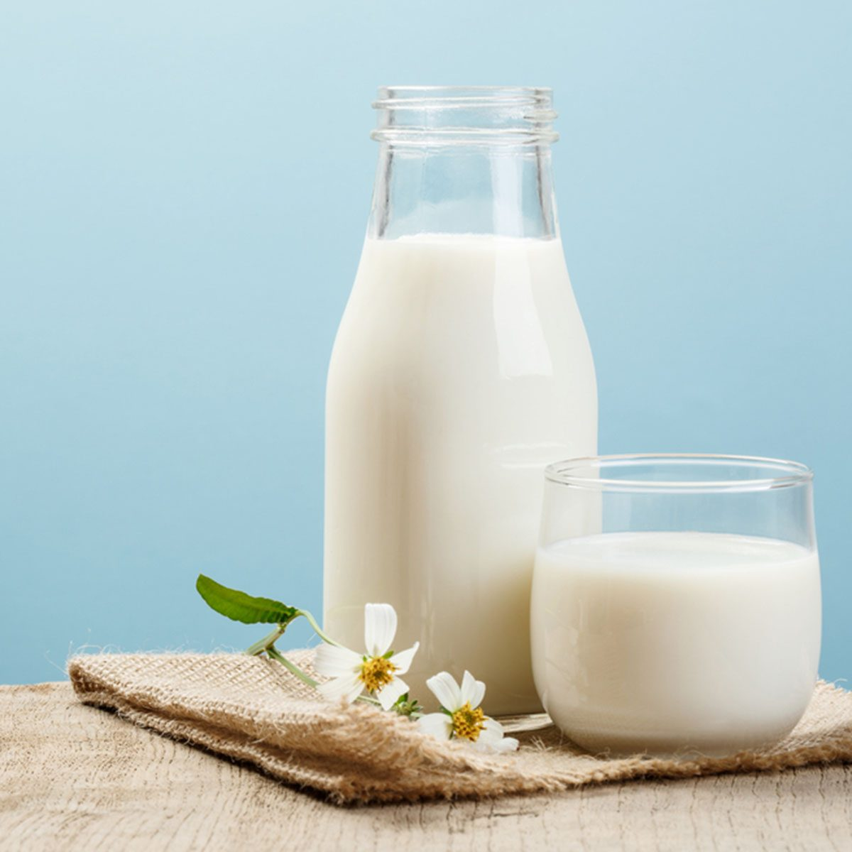 A bottle of milk and glass of milk on a wooden table on a blue background; Shutterstock ID 568076731