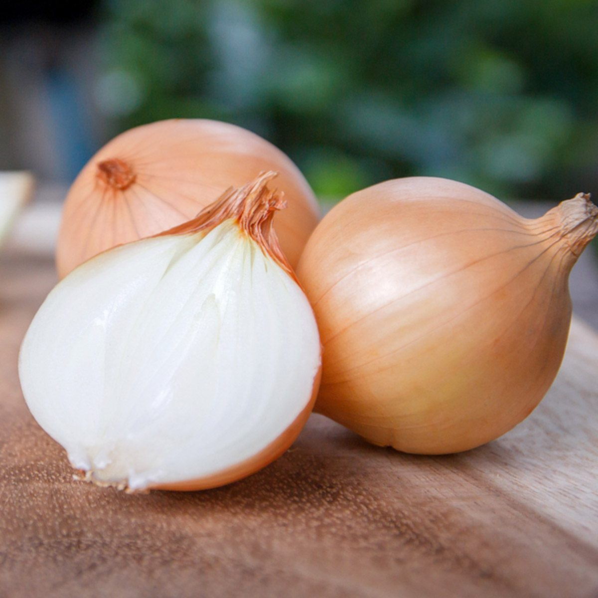 onion and onion slices on wooden cutting board.; Shutterstock ID 614533241
