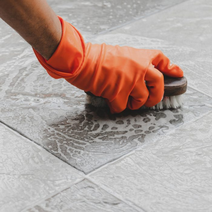 Hand of man wearing orange rubber gloves is used to convert scrub cleaning on the tile floor.; Shutterstock ID 1150384415; Job (TFH, TOH, RD, BNB, CWM, CM): TOH