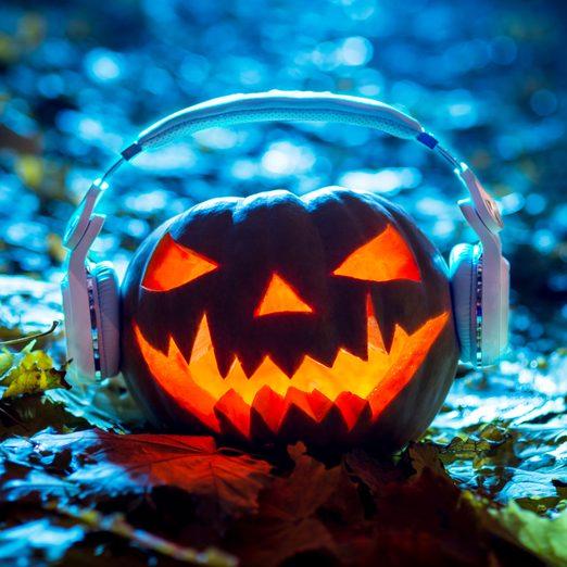 lit jack-o-lantern in the woods wearing headphones listening to a halloween music playlist