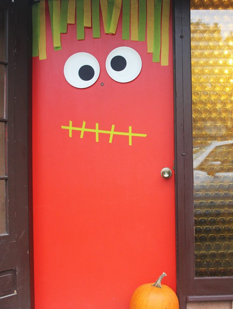 Bright red door with cut-out eyes and stripe of paper hanging down like hair