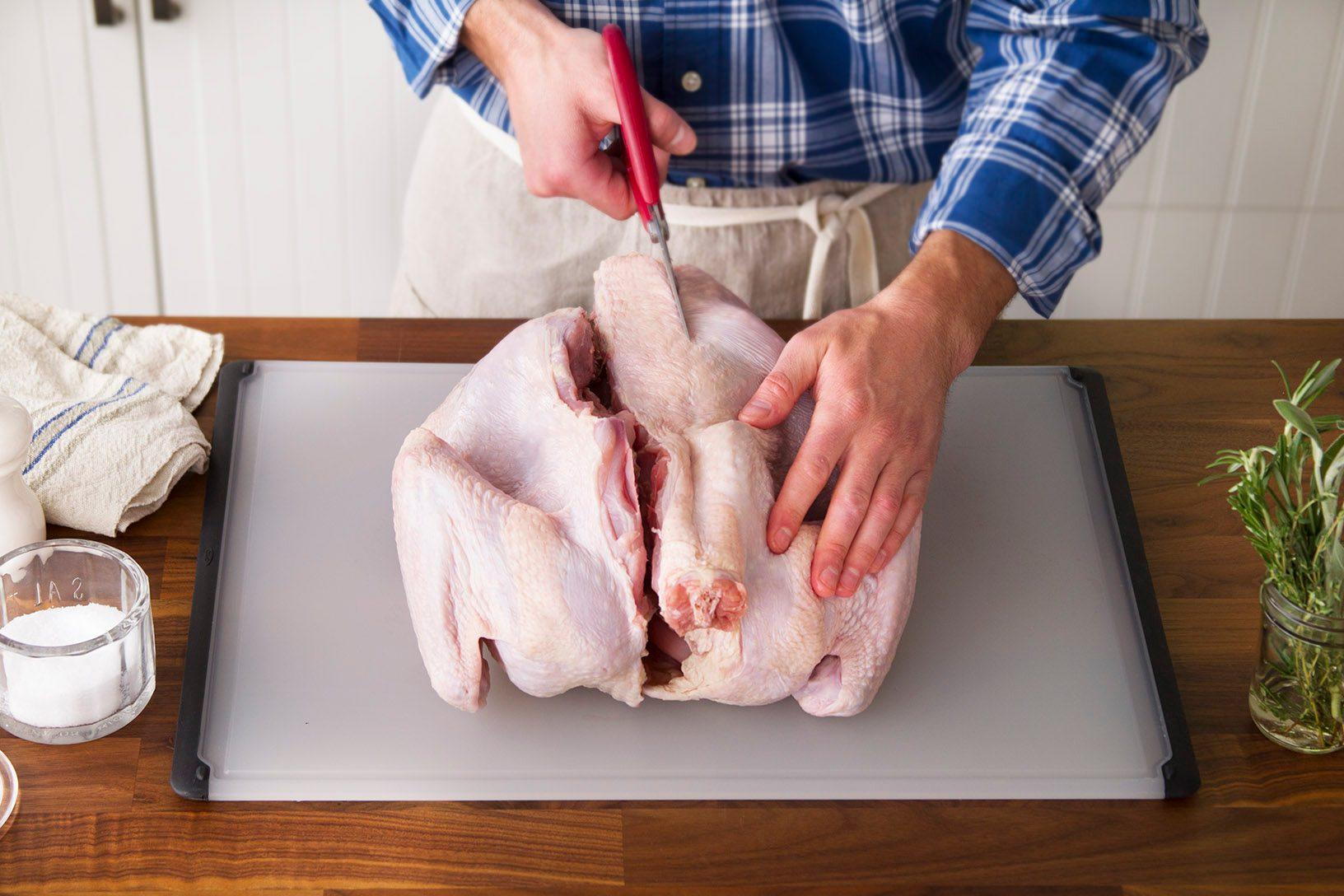 Person cutting the backbone out of a raw turkey carefully on a cutting board