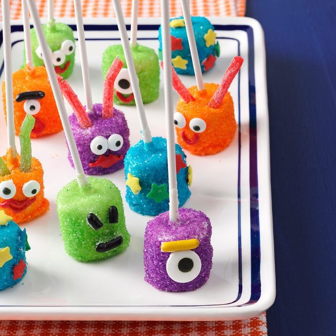 Marshmallows attached to lollipop sticks decorated as martians arranged on a plate.
