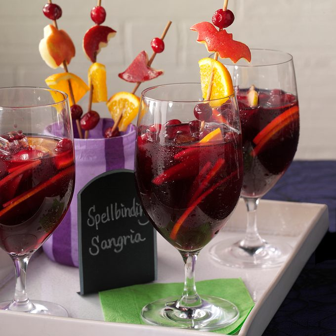 Three sangrias with fruit shaped like bats and pumpkins skewered and stuck inside
