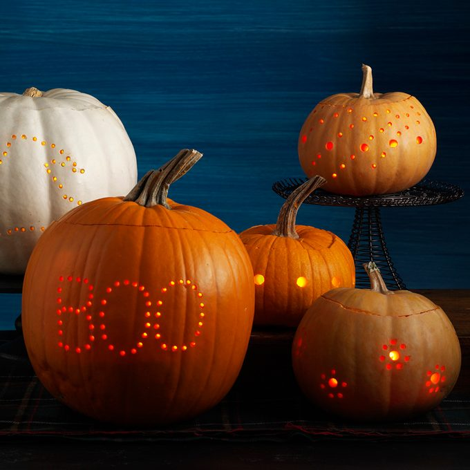 Five illuminated jack-o-laterns that are carved with mini holes that form different patterns and designs