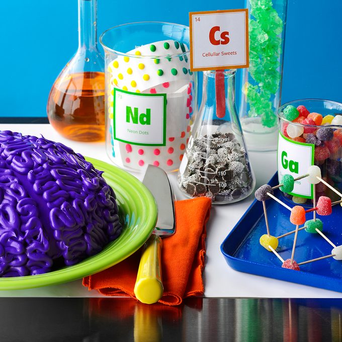 Purple 'brain' on a green plate surrounded by beakers and jars of labelled candy and juice