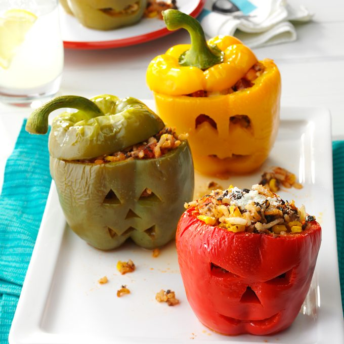 Three stuffed peppers in a row, each a different color and carved with jack-o-lantern faces