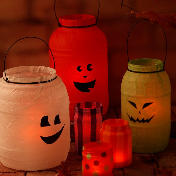 Mason jars covered in halloween-themed tissue paper like ghosts, jack-o-lantern and monsters lit up by candles