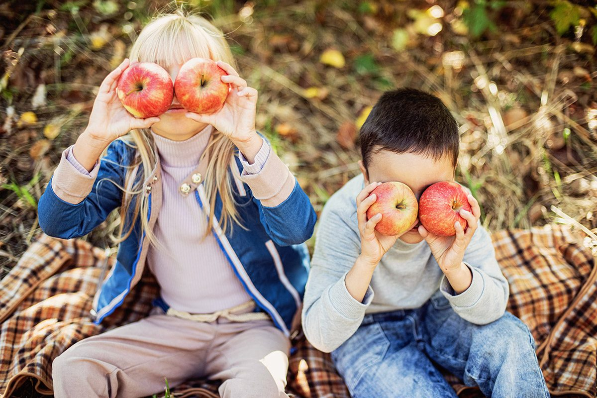 Children with Apple in Apple Orchard