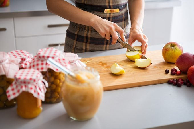 Closeup on young housewife cutting apple for jam;