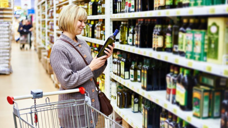 Woman reading the label on a bottle of olive oil in the store; Shutterstock ID 245223466; Job (TFH, TOH, RD, BNB, CWM, CM): TOH Cooking Oils