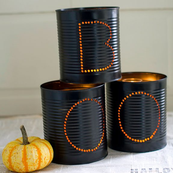 "Black cans stacked together with ""BOO"" written out in holes on them"