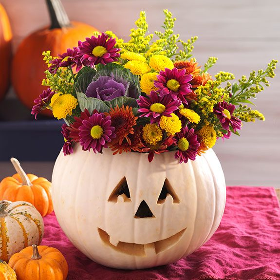 White jack-o-lantern with a bouquet of flowers popping out its top