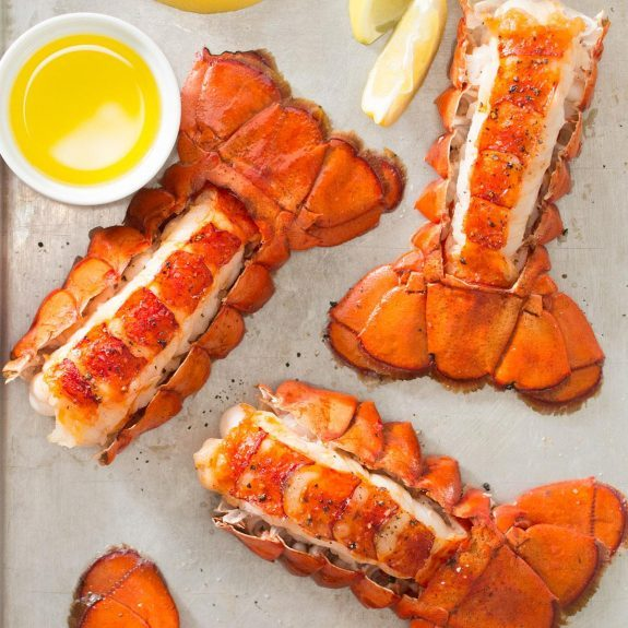 Four broiled lobster tails along with a small cup of melted butter