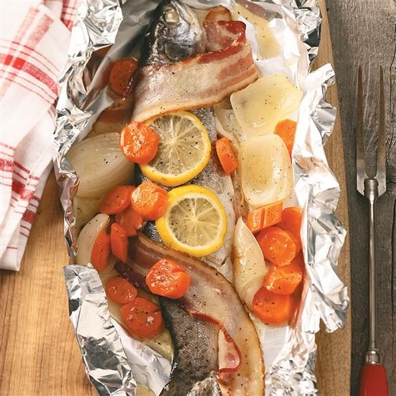 Whole trout wrapped in bacon, sliced lemons and carrots within a bed of tin foil