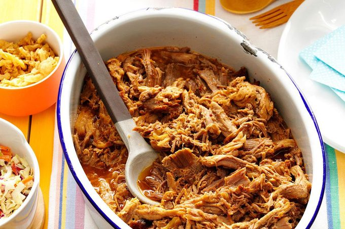Shredded pork in a white pot with a large spoon dug in deep
