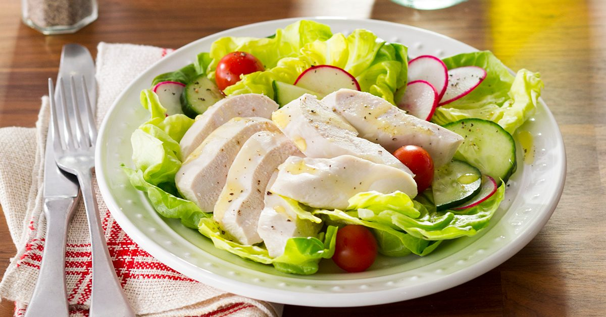 Poached chicken on a bed of lettuce and sliced radishes