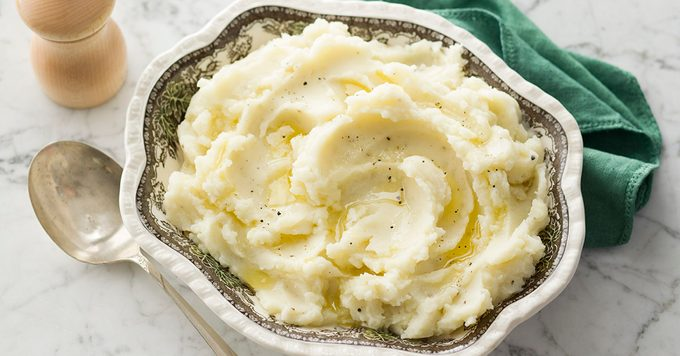 Mashed Potatoes in a white and grey bowl against a green napkin and spoon