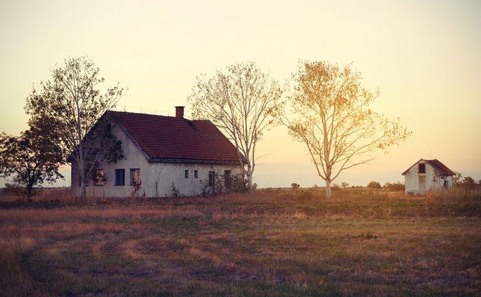Vintage photo of abandoned house at sunrise