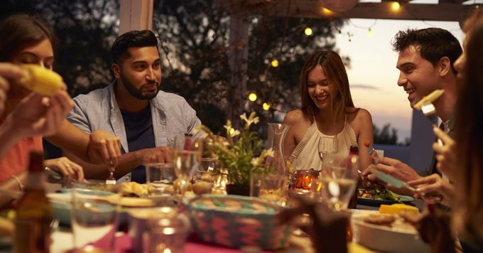 Friends eat and talk at a dinner party on a patio, close up
