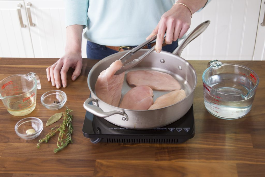 How to poach chicken with tons of flavor taste of home person placing raw chicken into a pan on the stovetop with metal tongs ccuart Gallery
