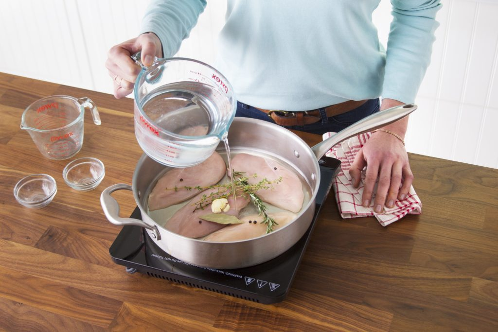 Person using a measuring cup to pour water into a pan on the stovetop filled with raw chicken