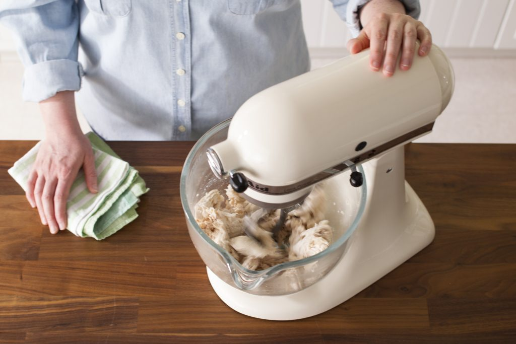 Chicken being shredded in a mixer on a wooden countertop
