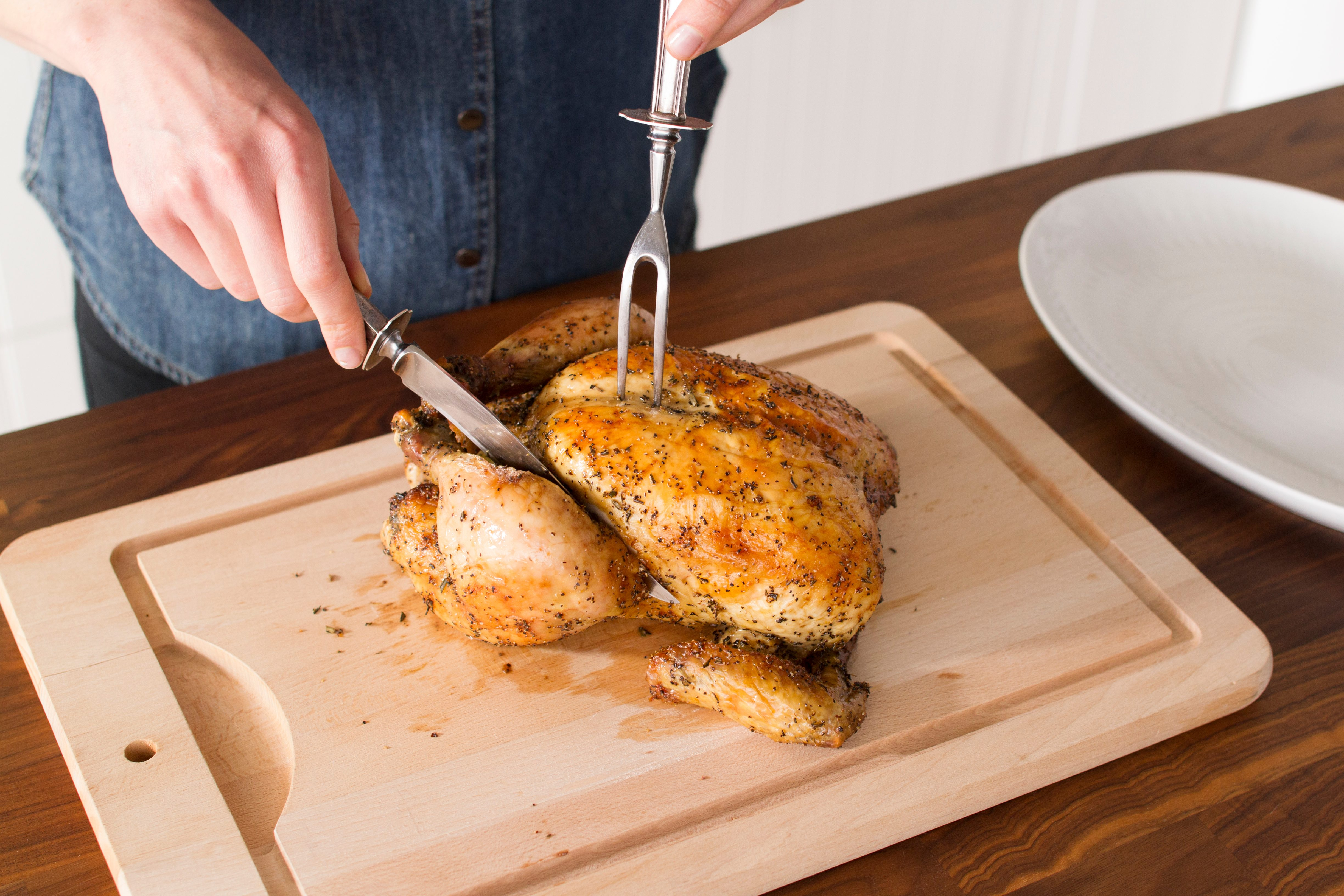 Person holding a whole cooked chicken down with a fork as they slice into one leg with a knife