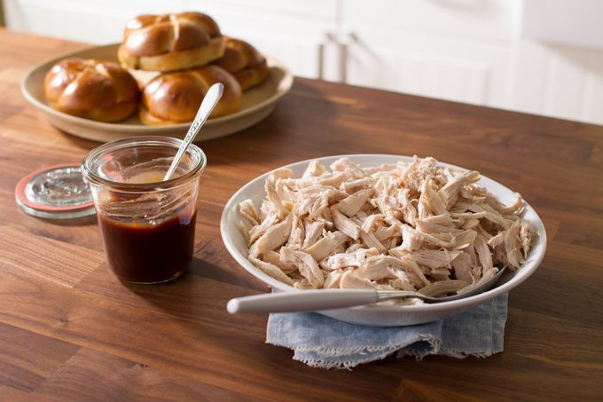 A white plate filled with shredded chicken on a wooden table beside a plate of buns and jar of gravy
