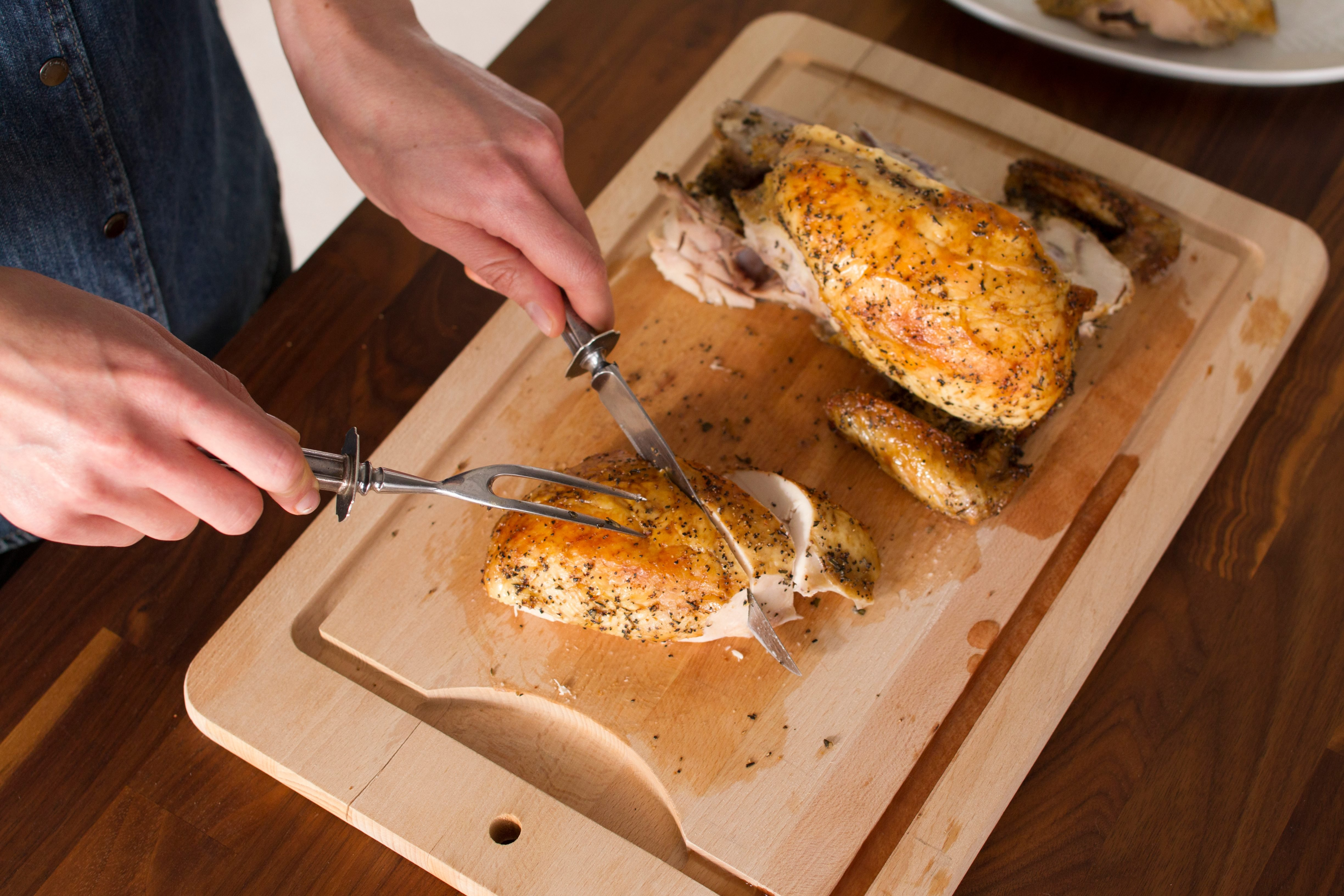 Person slicing into the chicken breast pieces on a wooden cutting board