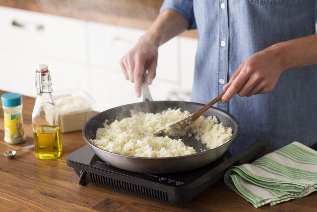 The cauliflower rice has hit the stovetop and is steaming deliciously as the cook stirs it with a wooden spoon