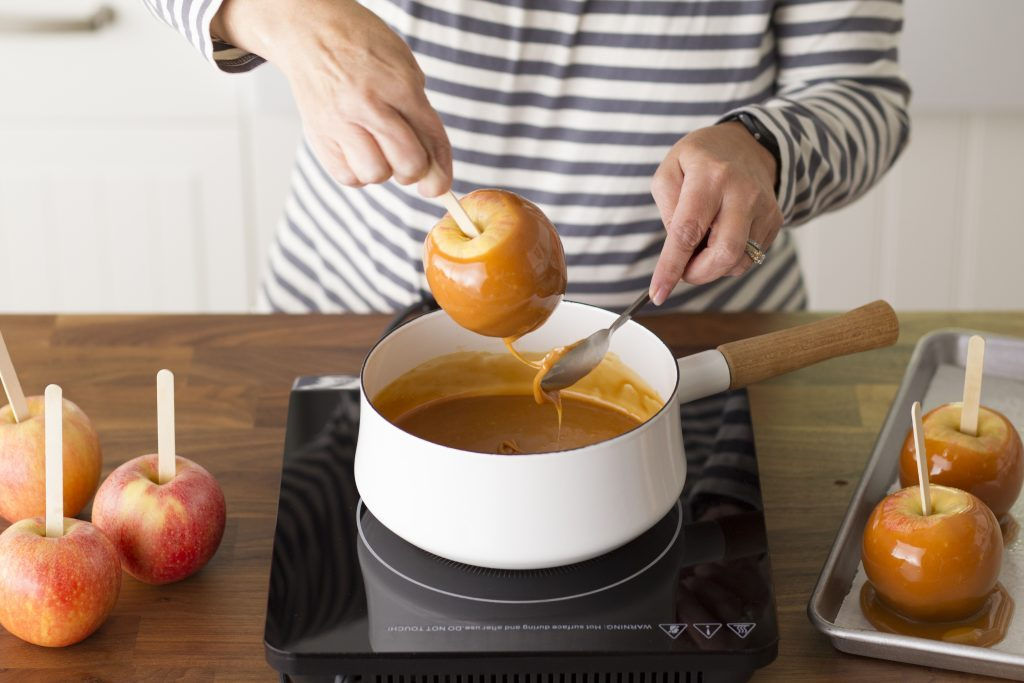 Person pulling a caramel apple out of a pot of melted caramel