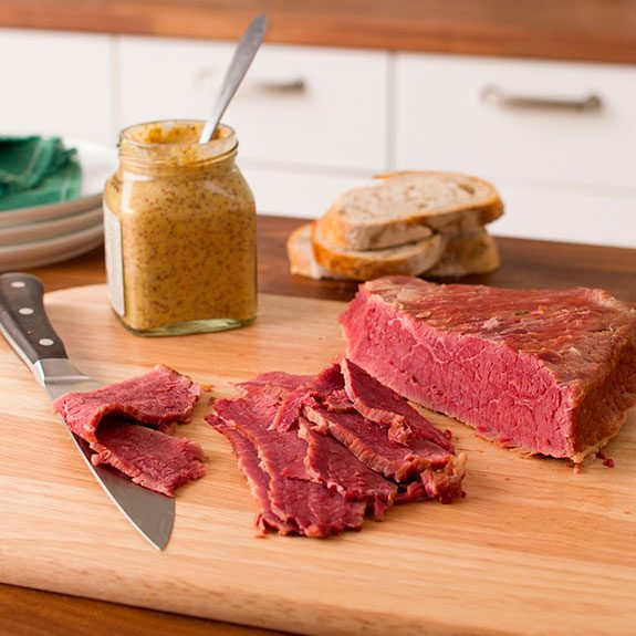 Slab of corned beef on a wooden cutting board with several slices laying in front