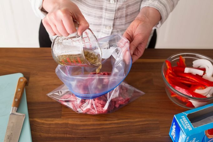 The sliced beef is now in a plastic bag having marinade poured over it